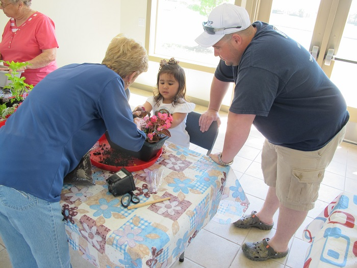 Gardeners from the Cyprus Creek Lake Garden Club near Houston help a child prepare a container garden during a Junior Gardener event, sponsored by a Community Champions grant from Constellation.